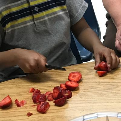 little kid cutting strawberries